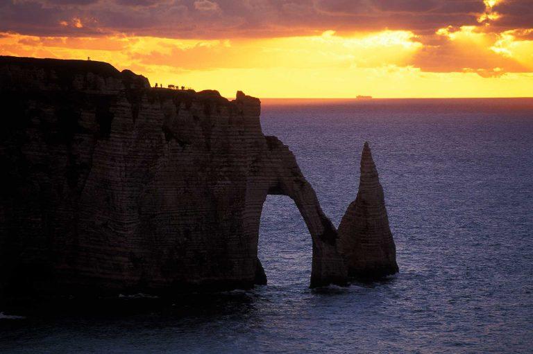 De kliffen Falaise d'Aval en l'Aiguille bij Etretat bij zonsondergang.