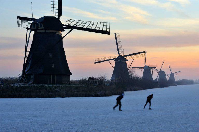 Molens en schaatsers bij Kinderdijk.