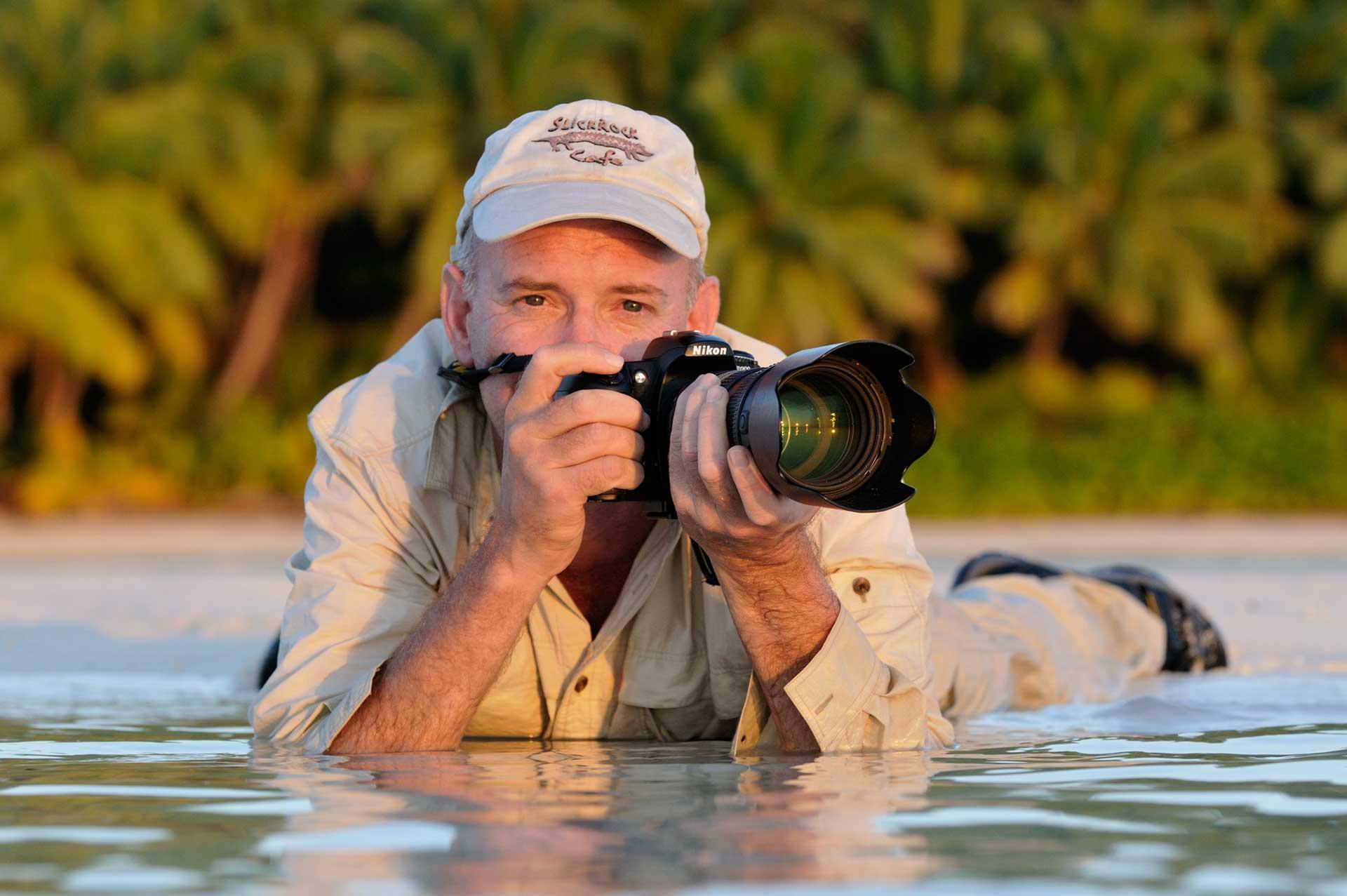 Martin van Lokven aan het werk op de Seychellen, fotograferend in water.